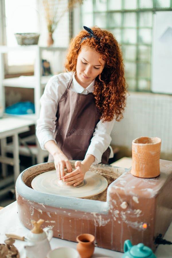 Potier roux formant l'argile dans le studio de poterie photos libres de droits