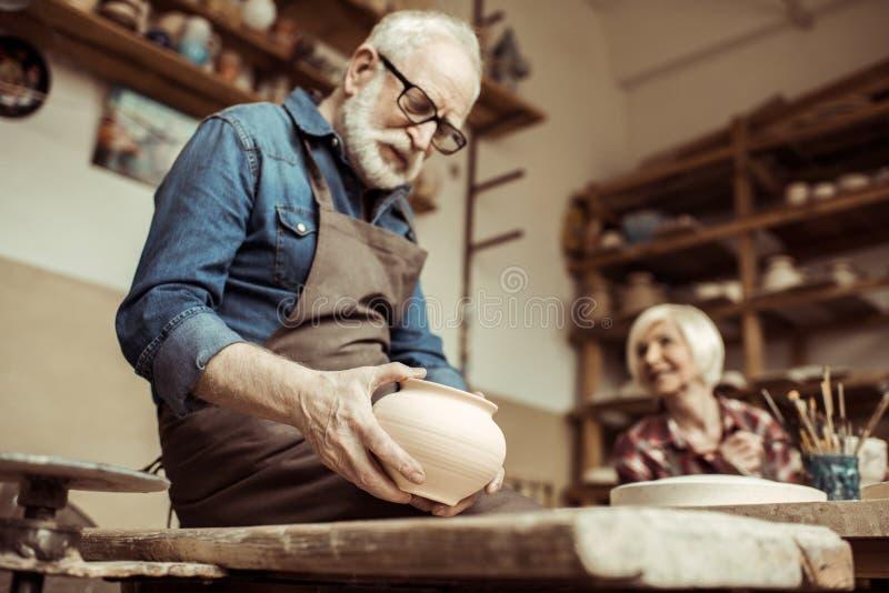 Potier supérieur dans le tablier et lunettes examinant la cuvette en céramique avec le fonctionnement de femme images stock