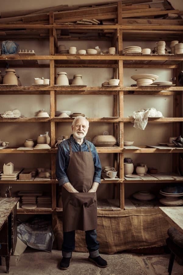 Potier supérieur dans le tablier se tenant contre des étagères avec des marchandises de poterie à l'atelier photos stock