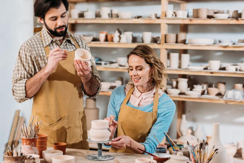potiers heureux peignant le dishware en céramique images stock