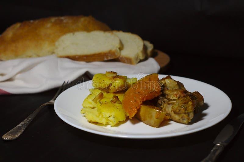 Potiron avec des pommes de terre et poulet sur un fond foncé photo stock