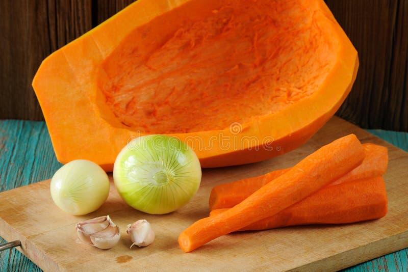 Potiron, carottes, oignons et ail doux épluchés sur le conseil en bois photos libres de droits