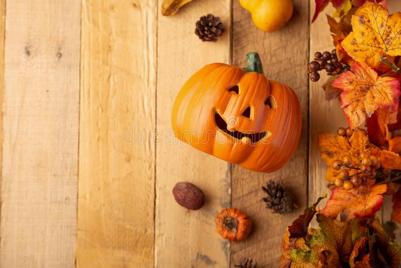 Potiron de Halloween avec des feuilles et des cônes de pin et éléments de décor sur une vieille table en bois Vue de ci-avant cad photographie stock