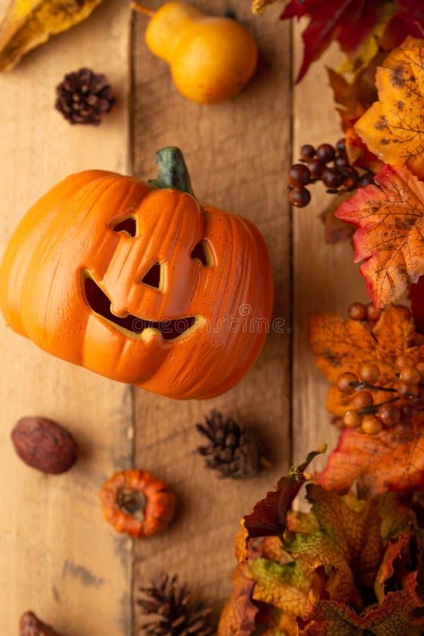 Potiron de Halloween avec des feuilles et des cônes de pin et éléments de décor sur une vieille table en bois Vue de ci-avant Cad image libre de droits