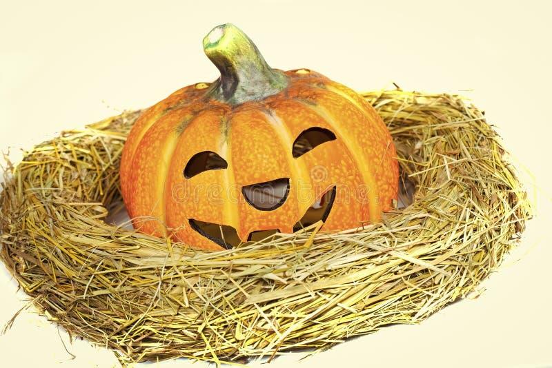 Potiron de Halloween avec le visage souriant en guirlande de paille photographie stock