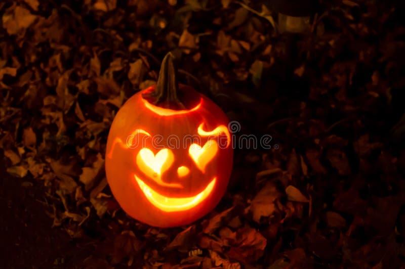 Potiron de Halloween souriant avec des coeurs dans des feuilles d'automne images libres de droits