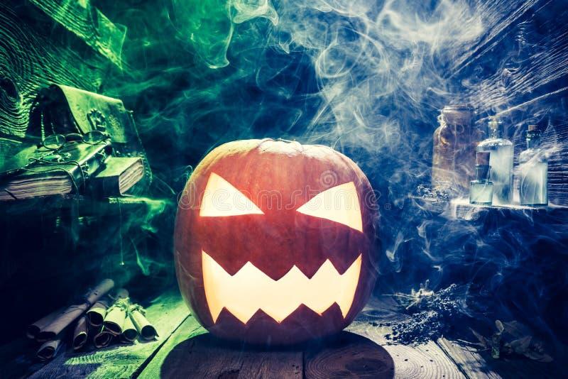 Potiron effrayant de Halloween avec de la fumée bleue et verte dans la hutte de witcher images libres de droits