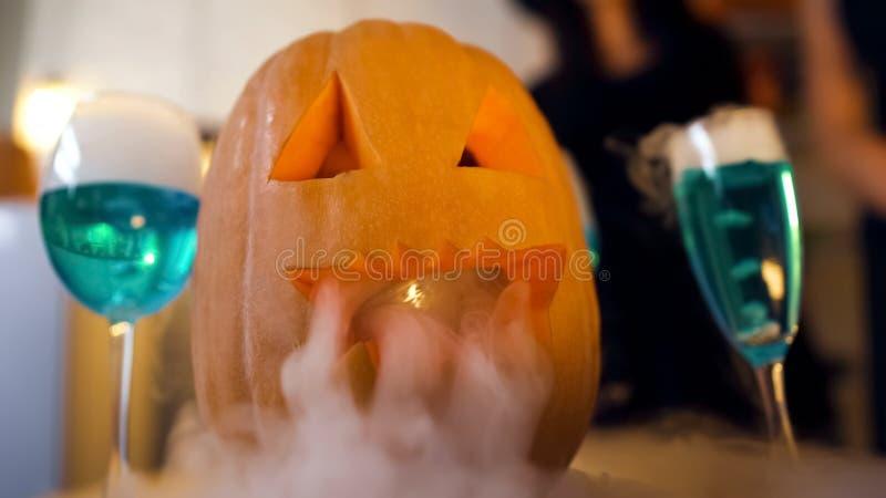 Potiron effrayant de Halloween et cocktails bleus fumeux sur la table de partie, traditions photo stock