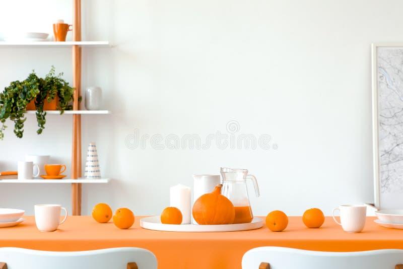 Potiron, oranges, tasses et pots sur la table de salle à manger couverte de nappe orange Mur vide blanc avec l'espace de copie photographie stock