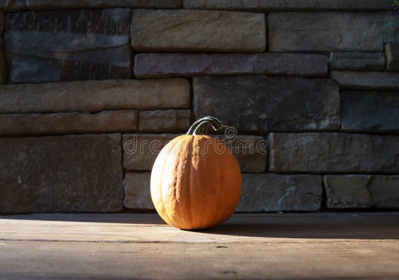 Potiron sur le porche en bois avec le fond de roche photos stock