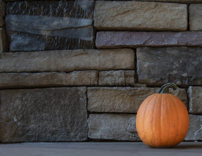 Potiron sur le porche en bois avec le fond de roche image libre de droits
