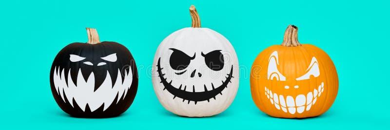 Potirons fantasmagoriques de Halloween avec des expressions effrayantes de visage au-dessus de fond bleu en pastel Bannière de co image libre de droits
