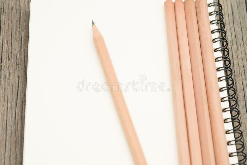 Potloden en notitieboekje op bureau stock afbeelding