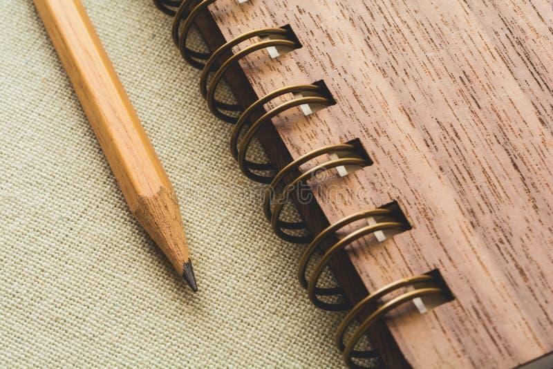 Potlood en spiraalvormig notitieboekje op de canvasachtergrond stock afbeelding
