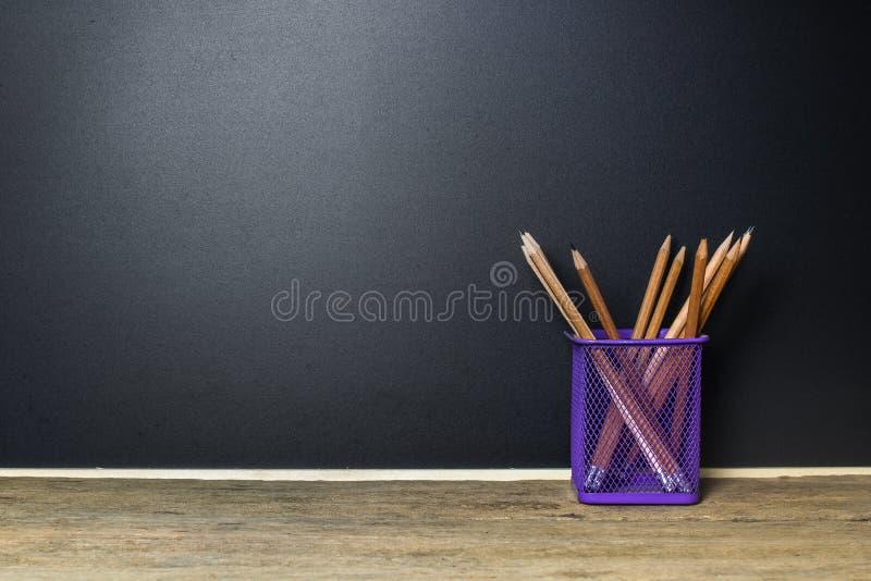 Potlood in mand op houten lijst met BordSchoolbord royalty-vrije stock fotografie