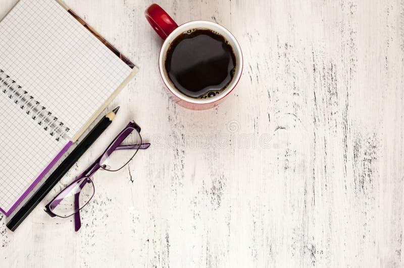 Potlood, notitieboekje, glazen en een kop van koffie op een witte houten lijst stock fotografie