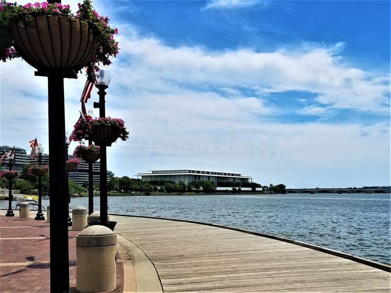 Potomac River View from Washington Harbor Boardwalk. A panoramic view of the Potomac River and Kennedy Center. Summer clouds float above the curved boardwalk of royalty free stock photo