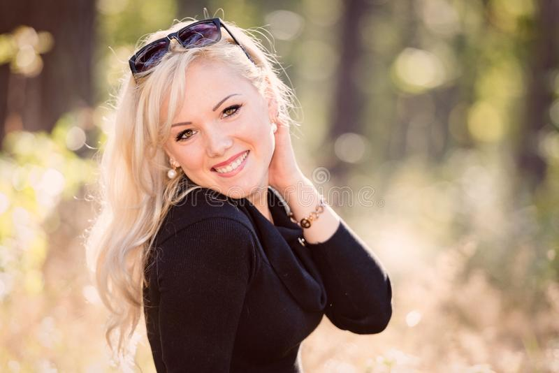 Potomstw, blond i uśmiechniętego kobieta portret na pogodnym jesień dniu, fotografia stock