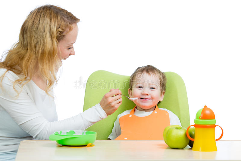 Potomstw matki łyżki karmienie jej chłopiec zdjęcie stock