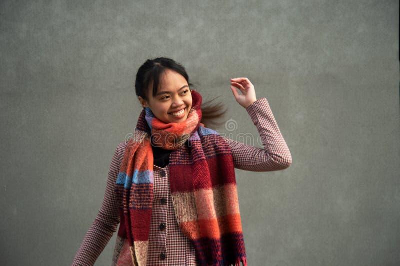 Potomstw 20s Azja długie włosy kobieta z kolorowym szalikiem na popielatej ścianie obraz stock