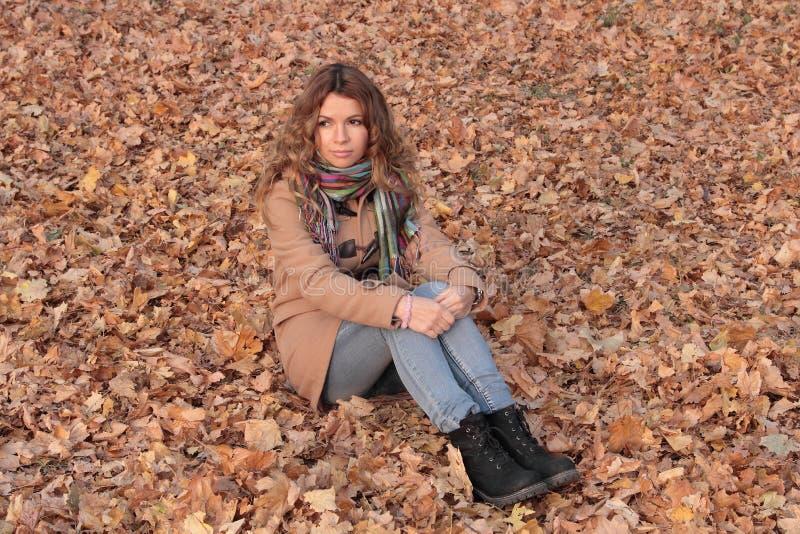 Potomstw, uśmiechniętej i ładnej kobieta w jesień parku, obrazy royalty free