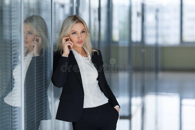 Potomstw, ufnej, pomyślnej i pięknej biznesowa kobieta z telefonem komórkowym, zdjęcie stock