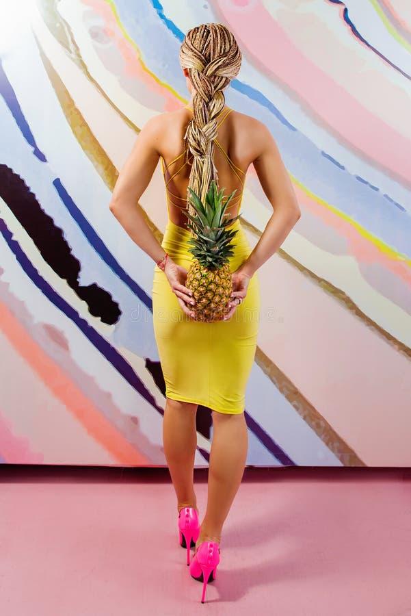 Potomstwa, śliczna, piękna szczupła blondynki kobieta z afrykanów warkoczami z ananasami w jej rękach i, obraz royalty free