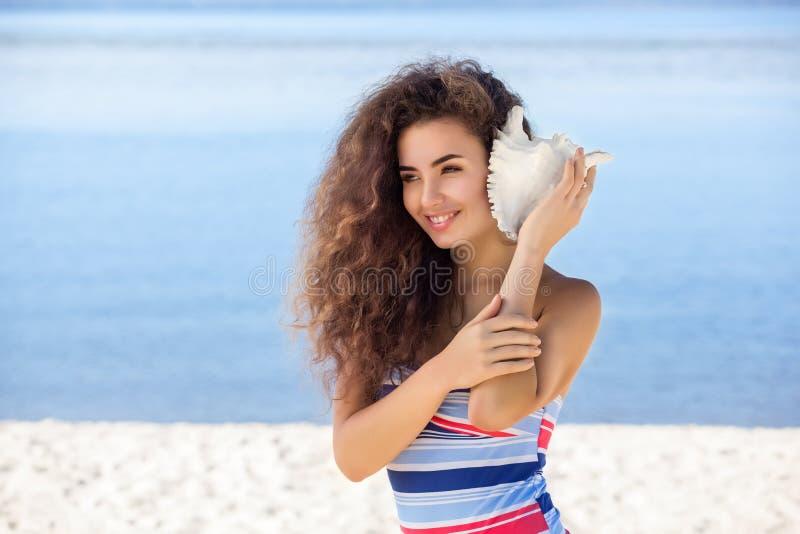 Potomstwa, atrakcyjna dziewczyna z białą skorupą na plaży obrazy royalty free