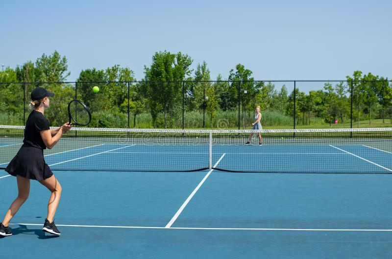 Potomstwa bawją się kobiety bawić się tenisa na błękitnym tenisowym sądzie obrazy royalty free