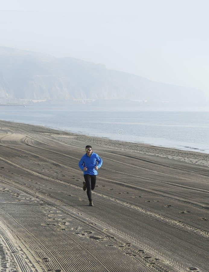Potomstwa bawją się mężczyzna biega samotnie na pustyni plaży wzdłuż dennego brzeg stażowego treningu obrazy stock