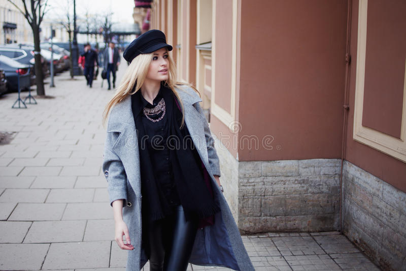 Potomstwa, blondynki odprowadzenie wokoło miasta, dziewczyna w eleganckim kapeluszu i szary żakiet, modny i atrakcyjny, zdjęcie royalty free