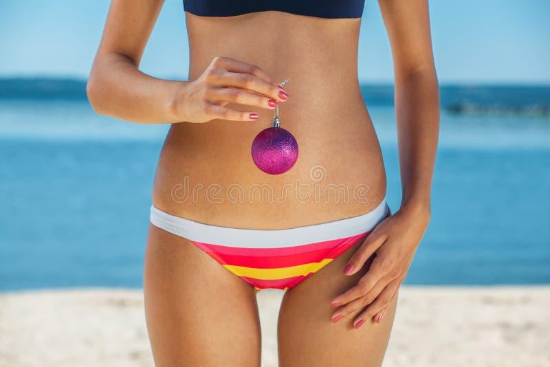 Potomstwa, chuderlawa, ładna dziewczyna trzyma różową Bożenarodzeniową piłkę w ręce w pasiastym kostiumu kąpielowym, na oceanie m fotografia royalty free
