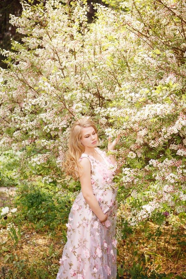 Potomstwa ciężarnego womani n kwieciste menchie ubierają stojący kwiatonośnych drzewa fotografia stock