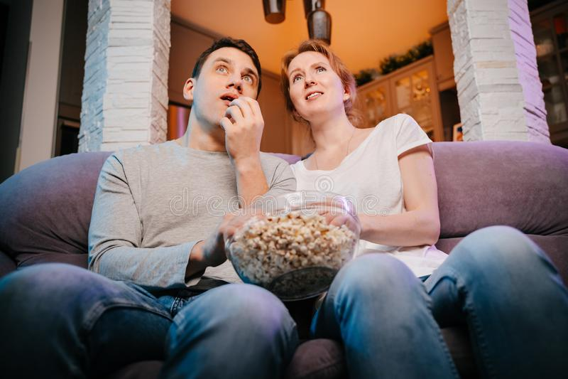 Potomstwa dobierają się łasowania dopatrywanie i popkorn w domu film na leżance, straszącej fotografia stock