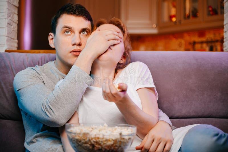 Potomstwa dobierają się łasowania dopatrywanie i popkorn w domu film na leżance, straszącej obrazy royalty free