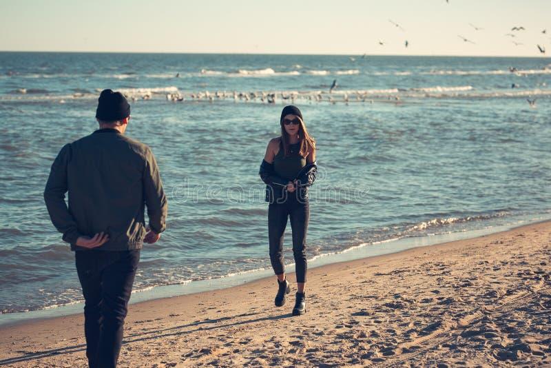 Potomstwa dobierają się w miłość spacerach morzem Wiosna, jesień Facet jest ubranym kapelusz i kurtkę Dziewczyna w skórzanej kurt fotografia royalty free