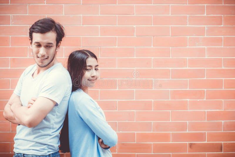 Potomstwa dobierają się azjatykcią atrakcyjną przyglądającą twarz i ono uśmiecha się popierać przeciw ściana z cegieł z romantycz zdjęcie royalty free