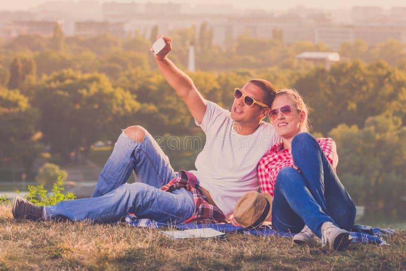Potomstwa dobierają się brać selfie na polu nad miasto fotografia stock