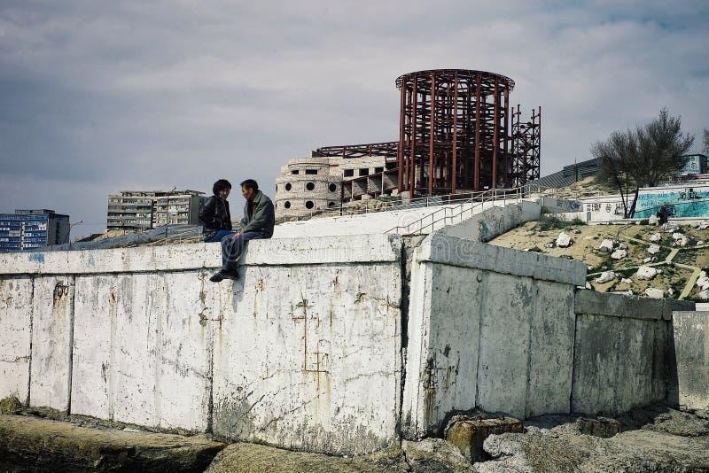 Potomstwa dobierają się gawędzenie i opowiadać na nadbrzeżu pustynny ex sowiecki miasteczko obraz royalty free