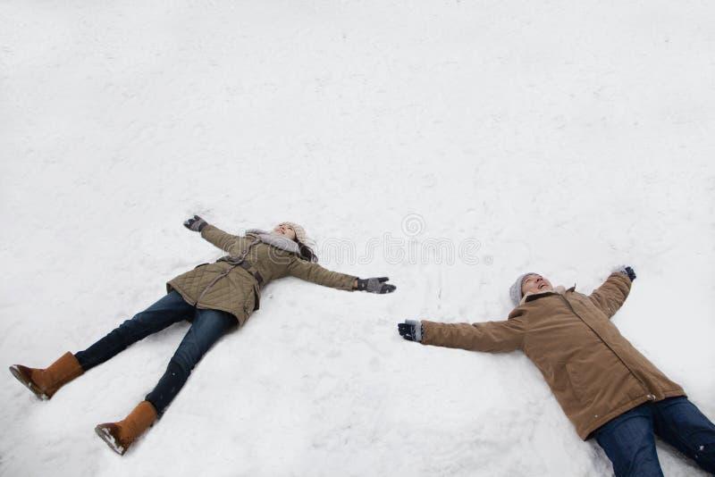 Potomstwa dobierają się kłaść w śniegu robi śnieżnym aniołom zdjęcie royalty free