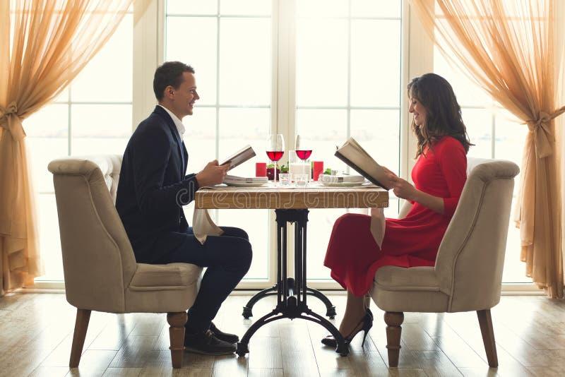 Potomstwa dobierają się mieć romantycznego gościa restauracji w restauracyjnym mienie menu zdjęcie stock