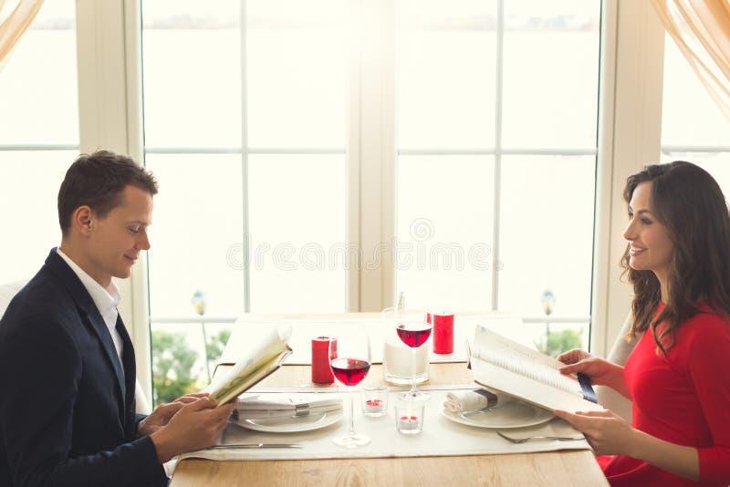 Potomstwa dobierają się mieć romantycznego gościa restauracji w restauracyjnym przegląda menu fotografia royalty free