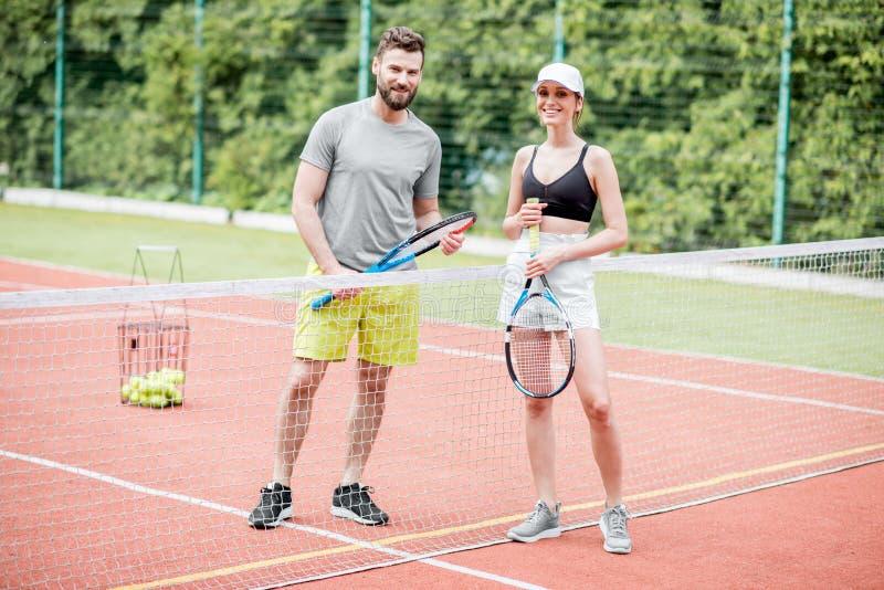 Potomstwa dobierają się mieć zabawy pozycję na tenisowym sądzie zdjęcie royalty free