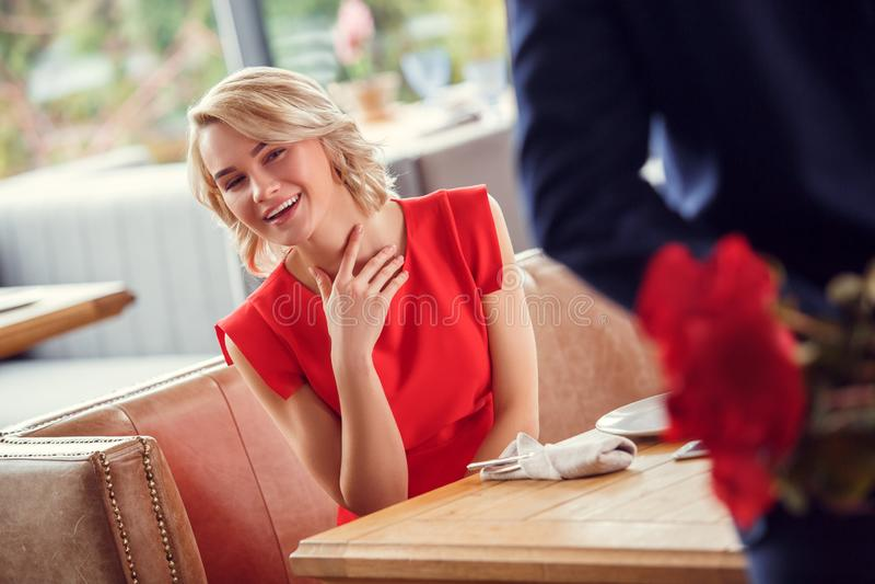 Potomstwa dobierają się na dacie w restauracyjnej kobiecie siedzi patrzeć ciekawi za mężczyzną chuje bukiet przy plecy w górę obrazy stock
