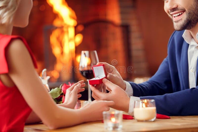 Potomstwa dobierają się na dacie w restauracyjnej obsiadanie mężczyzny ofercie kobieta rozochocona w górę jego rękę obraz stock