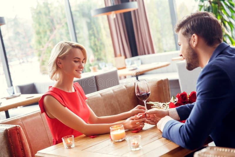 Potomstwa dobierają się na dacie w restauracyjnym obsiadanie mężczyźnie daje małemu teraźniejszości pudełku kobieta szczęśliwa fotografia stock