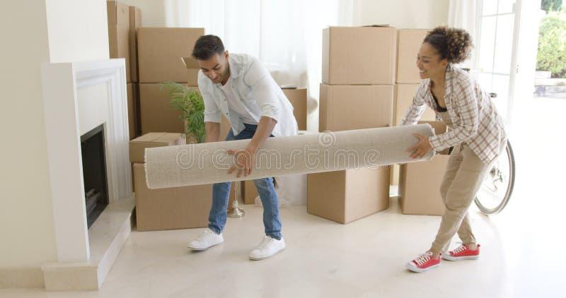 Potomstwa dobierają się nieść staczającego się dywanika w dom fotografia stock
