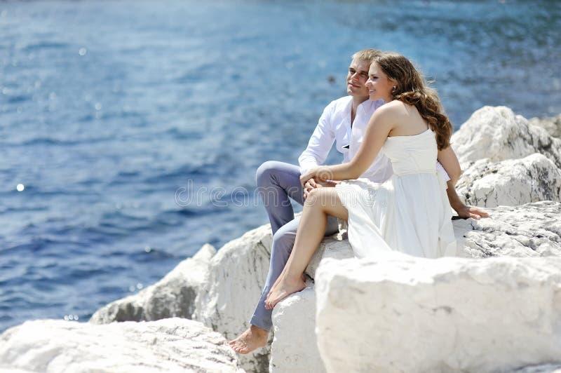 Potomstwa dobierają się obsiadanie na skałach blisko morza, Naples, Włochy obrazy royalty free