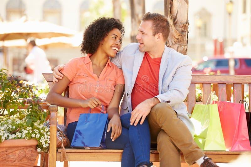 Potomstwa Dobierają się Odpoczywać Z torba na zakupy Siedzi W centrum handlowym zdjęcia royalty free