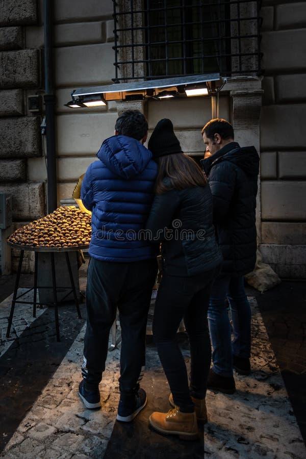 Potomstwa dobierają się odprowadzenie na ulicie przy wintertime, kupienie piec kasztany obrazy royalty free